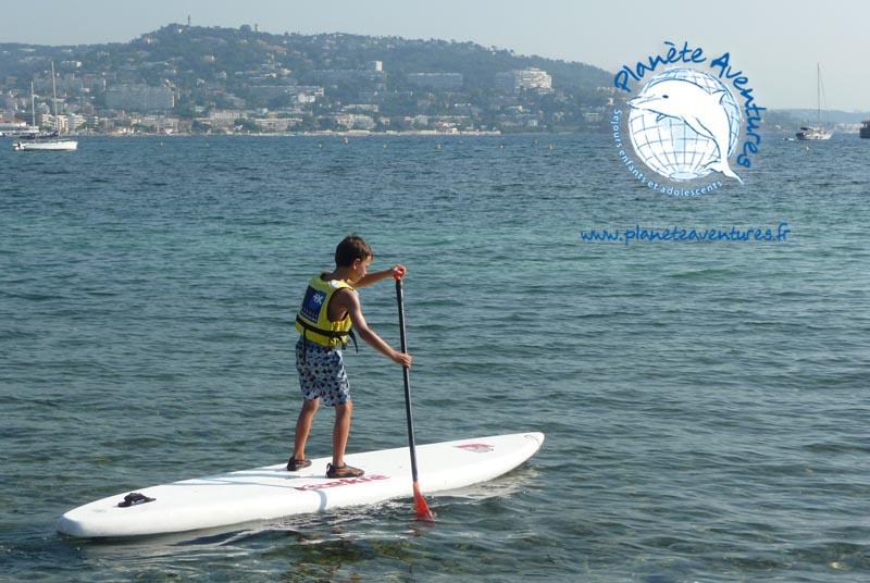 Un petit garçon se tient droit debout sur son standup paddle en bord de mer.